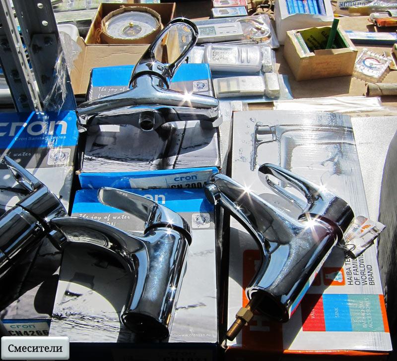 Интернет-магазин «SWG» - краны со смесителями лежат на витрине при солнечном свете. Оптовый рынок в Митино.